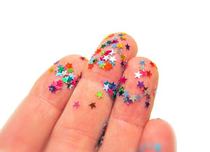 Image of a hand with stars glitter on fingertips